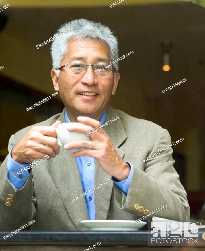 Stock Photo: Senior Asian businessman holding cup of coffee.