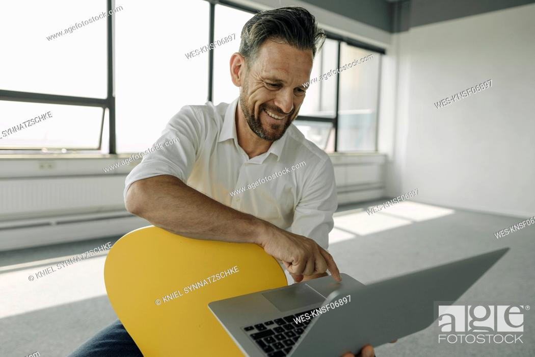 Stock Photo: Smiling mature businessman using laptop in empty office.