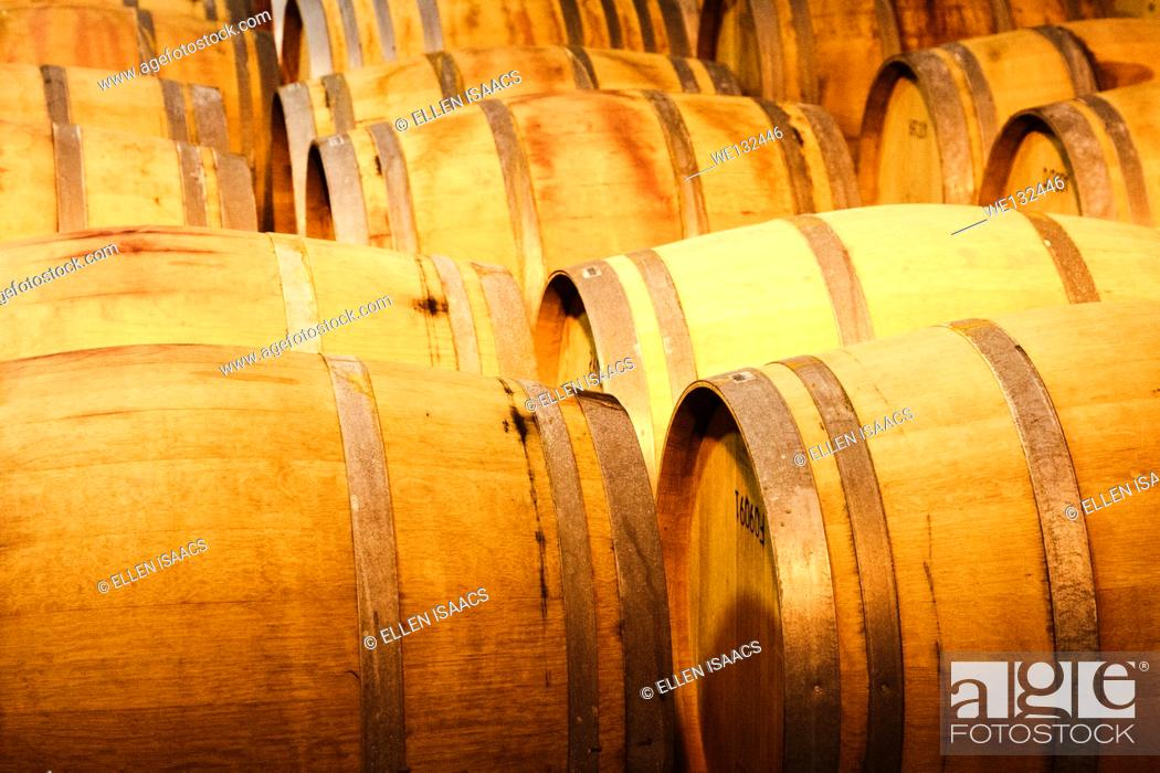 Stock Photo: Wooden barrels of wine being stored at a vineyard cellar.