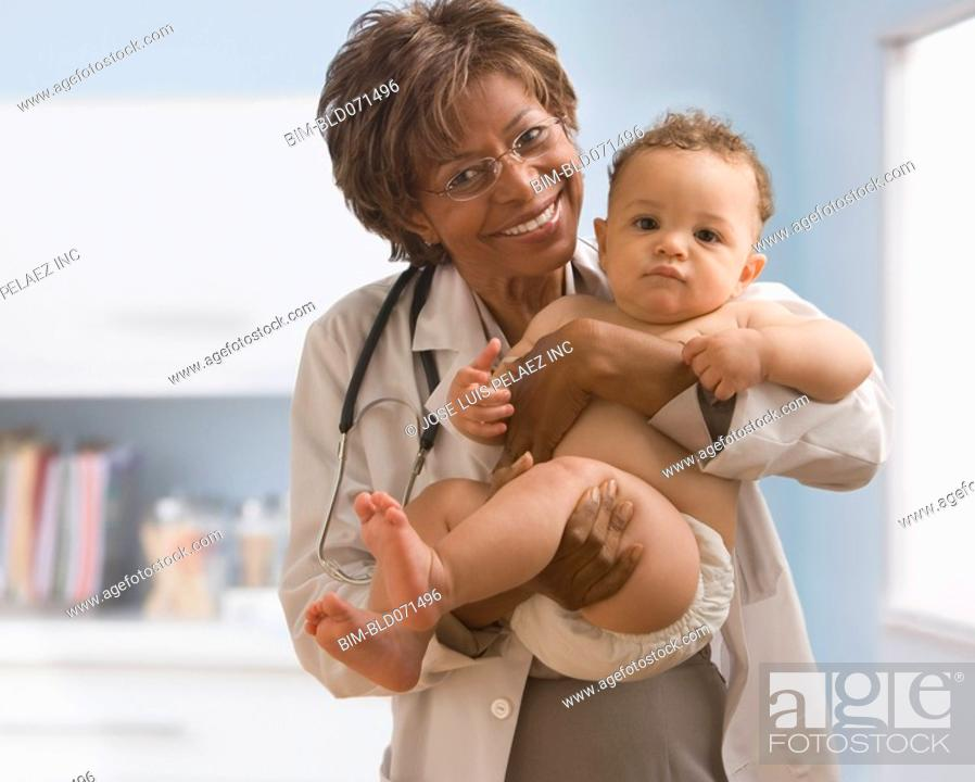 Stock Photo: African American female doctor holding baby.