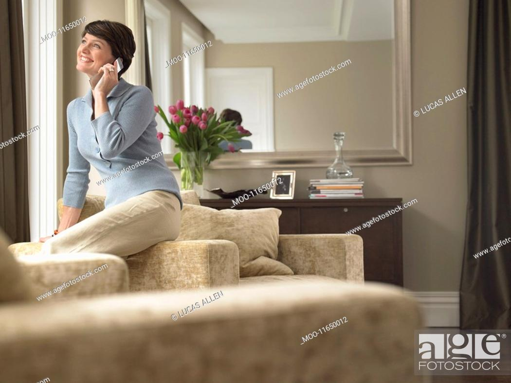 Stock Photo: Smiling woman talking on mobile phone in living room.