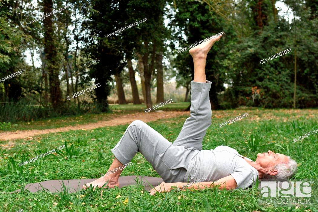 Stock Photo: elderly woman practicing yoga outdoors.