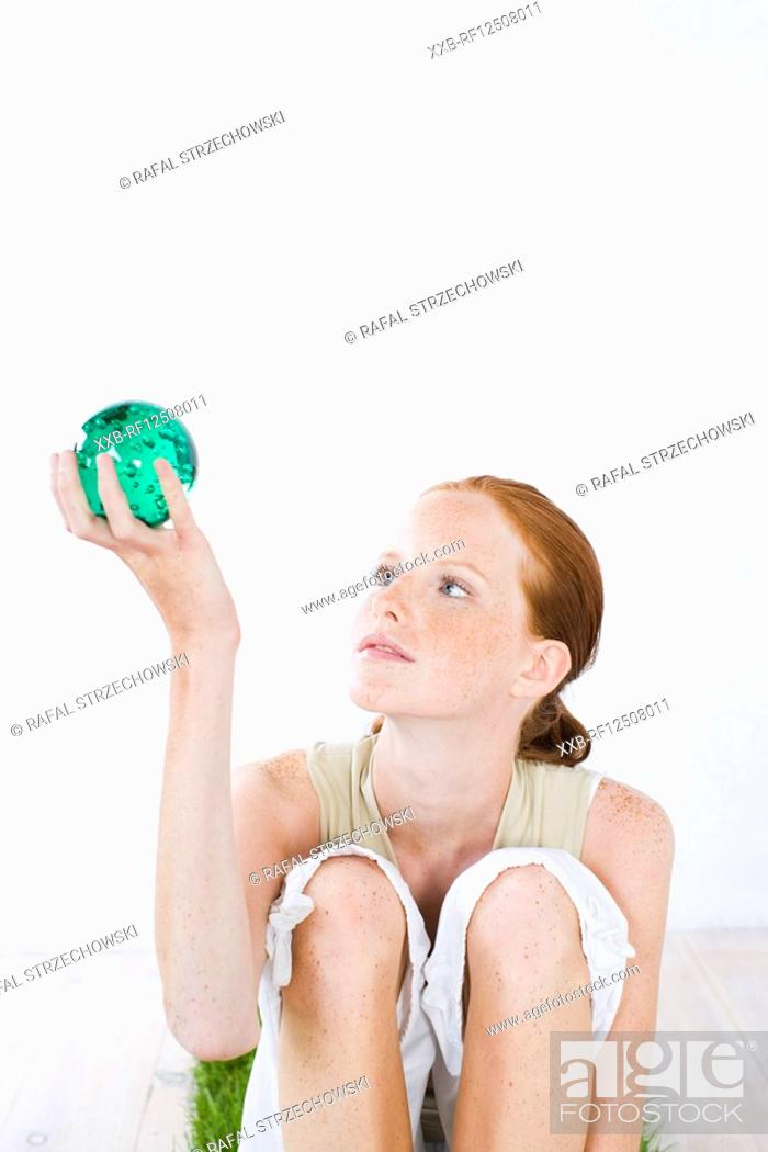 Stock Photo: young woman holding green ball.