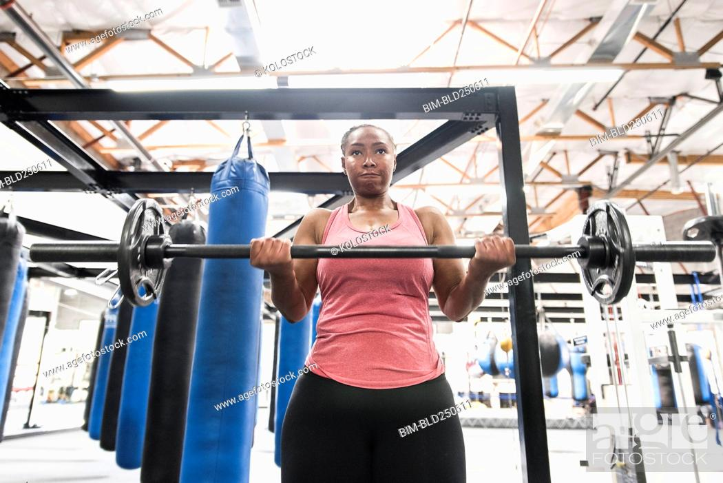Stock Photo: Black woman lifting barbell in gymnasium.