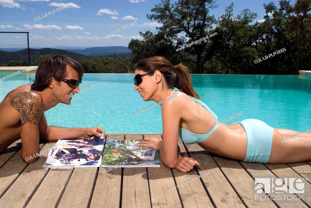 Couple sunbathing by a swimming pool with magazines, Stock ...