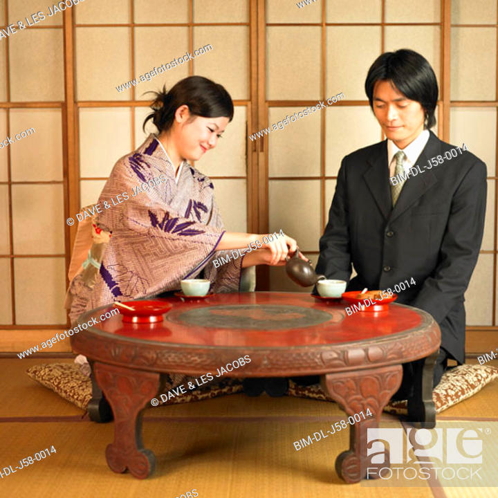 Stock Photo: Asian woman pouring tea for businessman.
