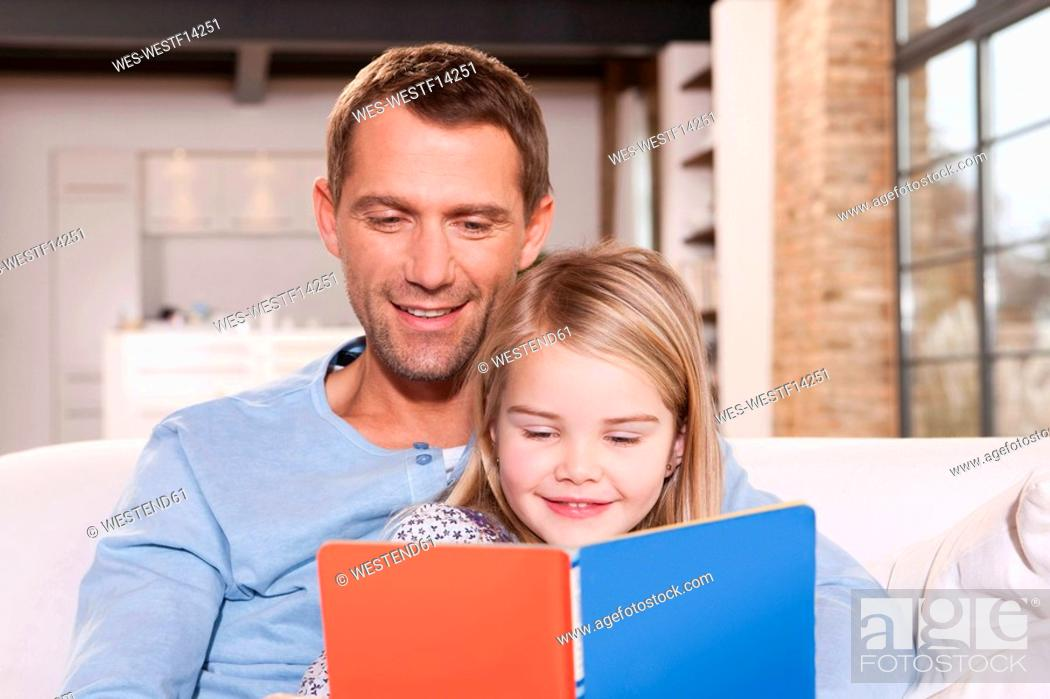 Stock Photo: Germany, Cologne, Father and daughter 6-7 reading book on sofa, portrait, close-up.