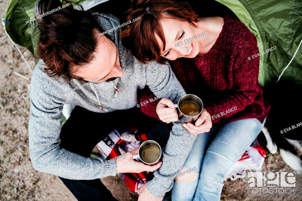 Photo de stock: Happy couple holding mugs at a tent.