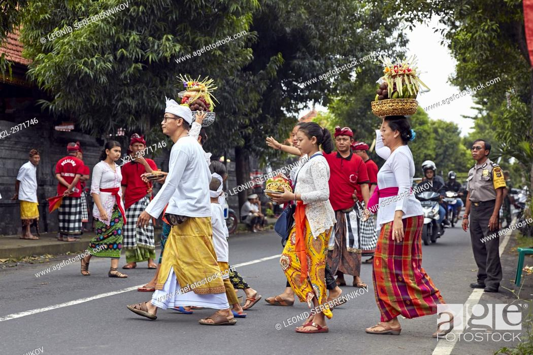 People Wearing Traditional Balinese Clothing Go To A Local Temple