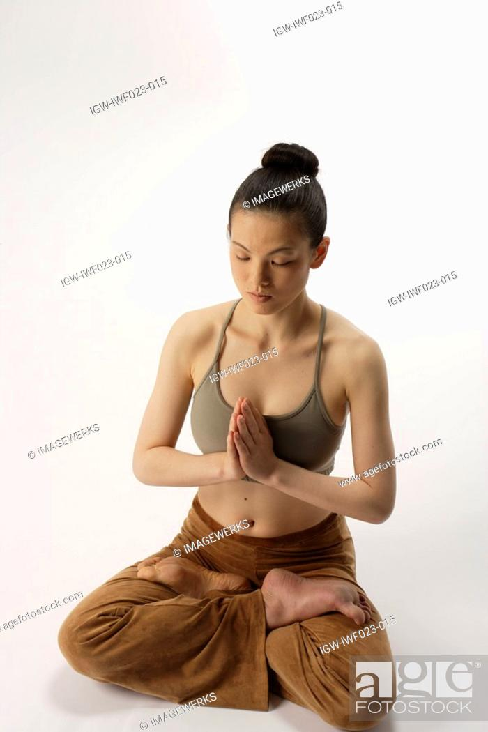 Stock Photo: High angle view of a young woman in lotus position.