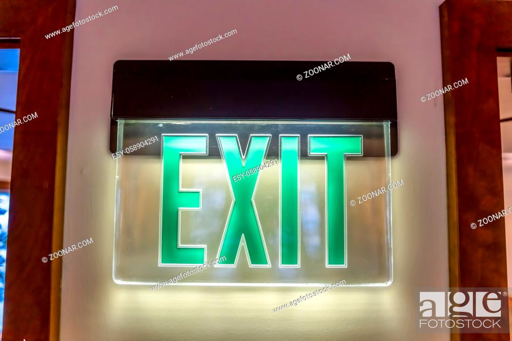 Stock Photo: Building interior with a neon green light Exit sign pounted on the white wall. The sign is flanked by doorways with brown wooden frames.