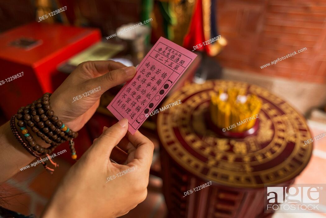 Imagen: Chinese young woman trying the traditional roll of fortune in a Buddhist temple; Shanzidou, Kinmen Island, Taiwan.