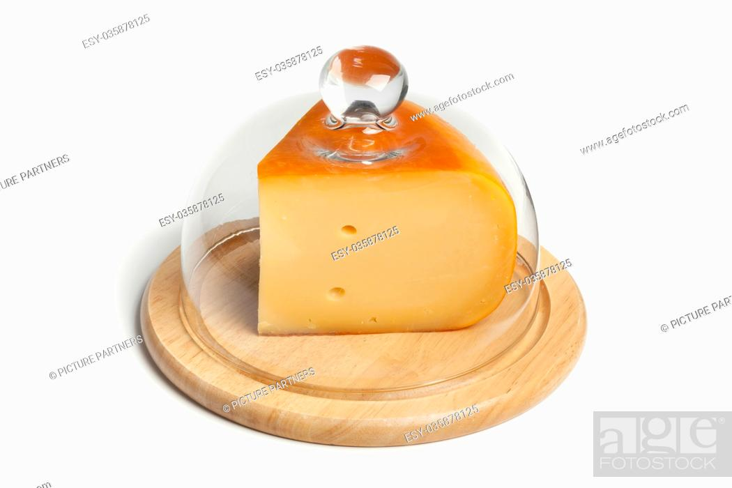 Photo de stock: Piece of Dutch Gouda cheese on a wooden board covered with a glass hood.