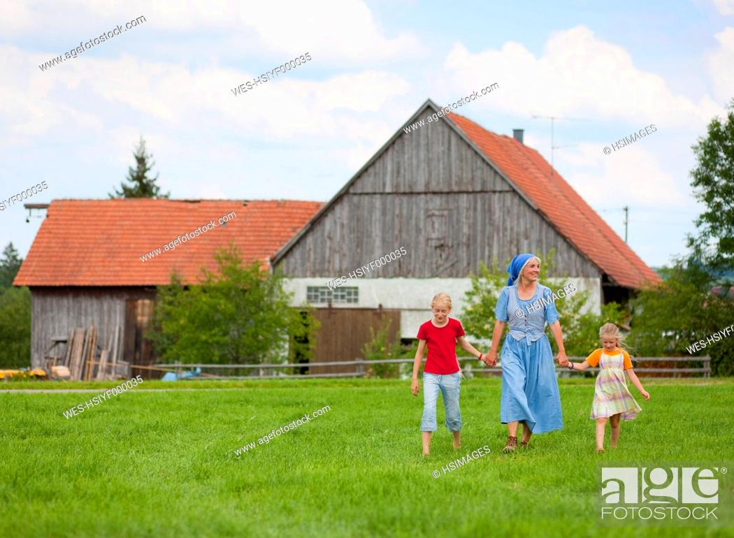 Stock Photo: Germany, Bavaria, Grandmother with children walking in front of farmhouse.