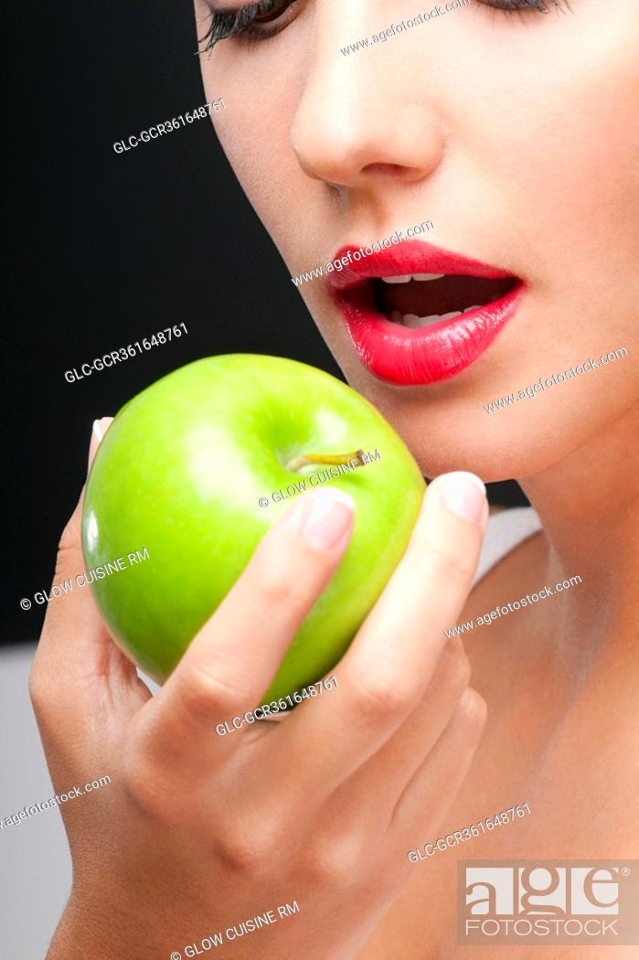 Stock Photo: Close-up of a woman eating a granny smith apple.