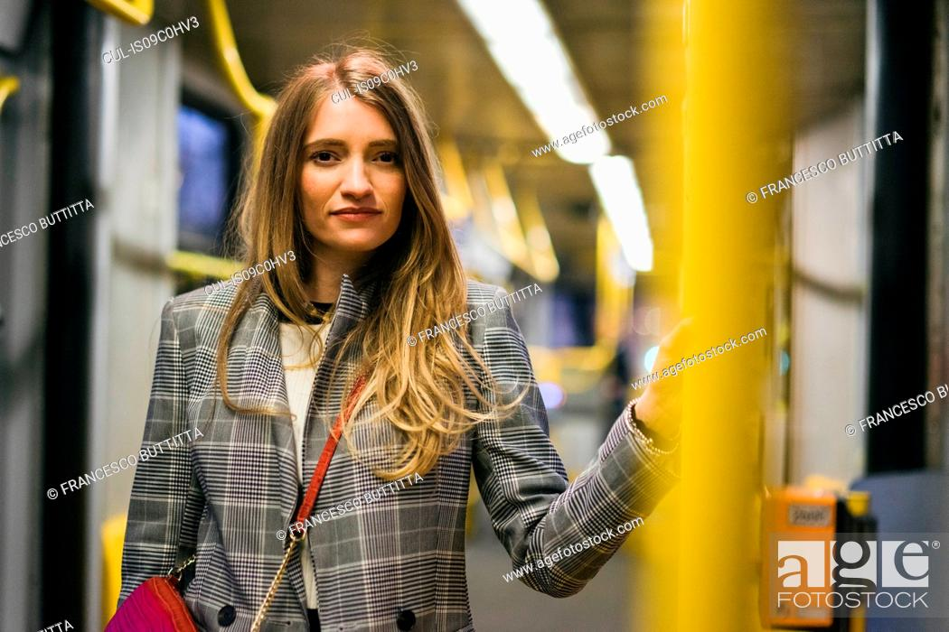 Stock Photo: Young woman with long blond hair standing in train carriage, portrait.
