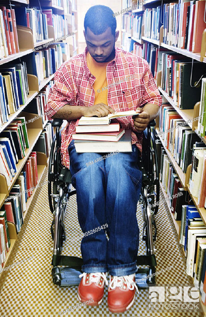 Stock Photo: Male college student in wheelchair at library.