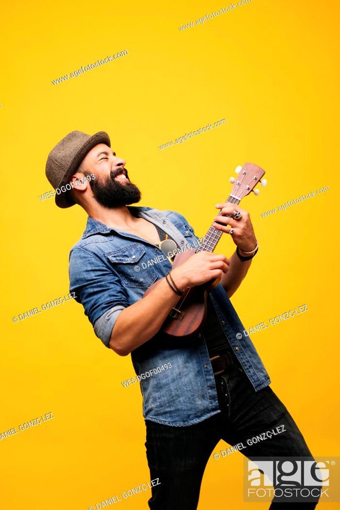 Imagen: Passionate young man in studio playing ukulele.