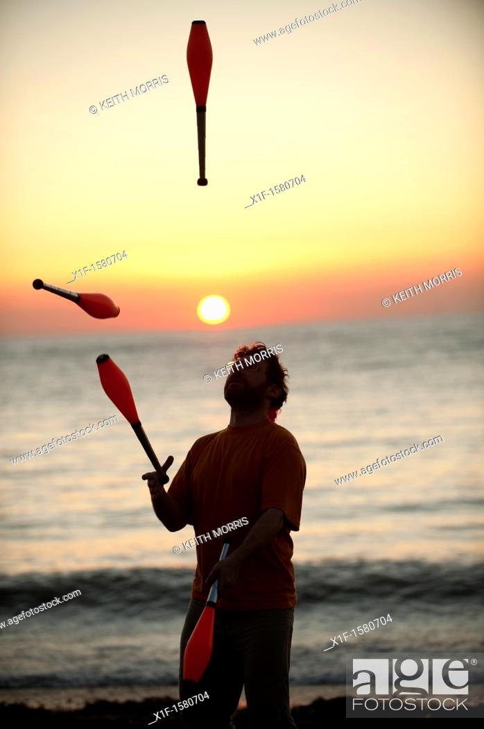 Stock Photo: A man juggling at sunset on the beach on a very warm late september evening Aberystwyth Wales UK.