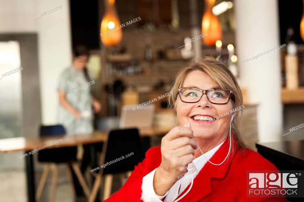 Stock Photo: Happy businesswoman talking through earphones at restaurant.