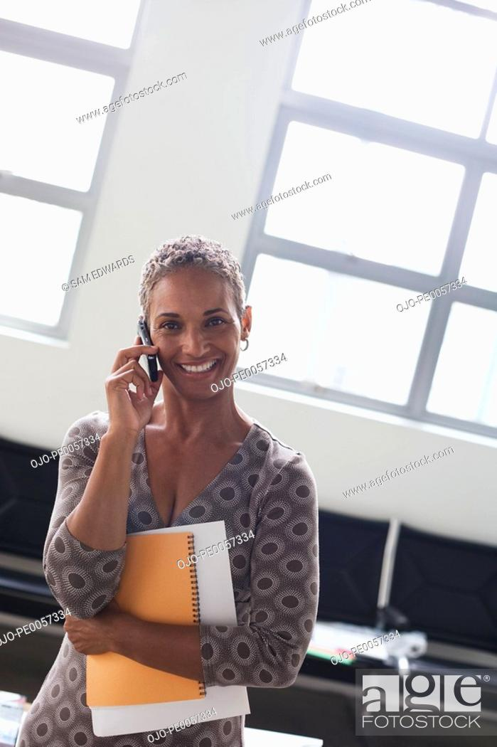 Stock Photo: Businesswoman on cellular phone in office.