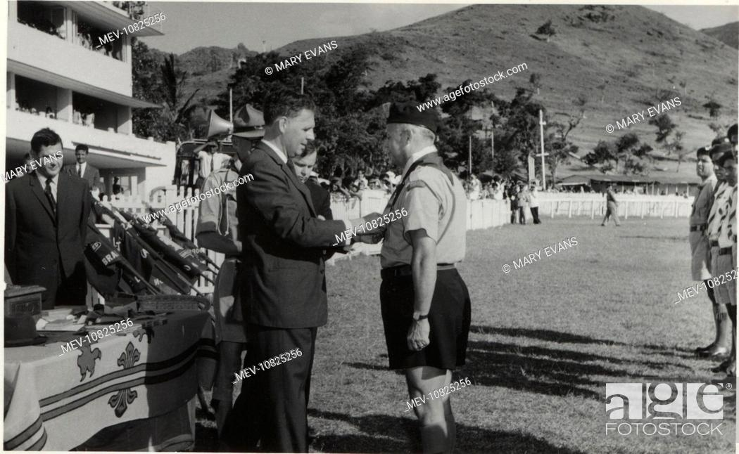 Stock Photo: The Governor of Mauritius, Sir John Shaw Rennie (1917-2002), presenting scouting leader Guy de la Hogue with the Silver Acorn at a rally.