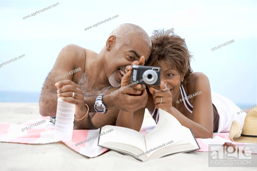 Stock Photo: Mature couple looking at digital camera on beach.