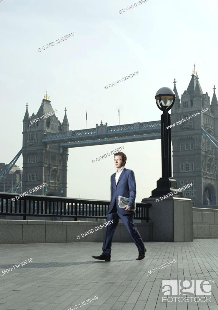 Stock Photo: Young business man walking in front of Tower Bridge.