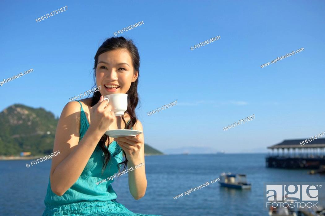 Stock Photo: Young Lady on Bench by Sea, Drinking Cup of Tea, Smiling.