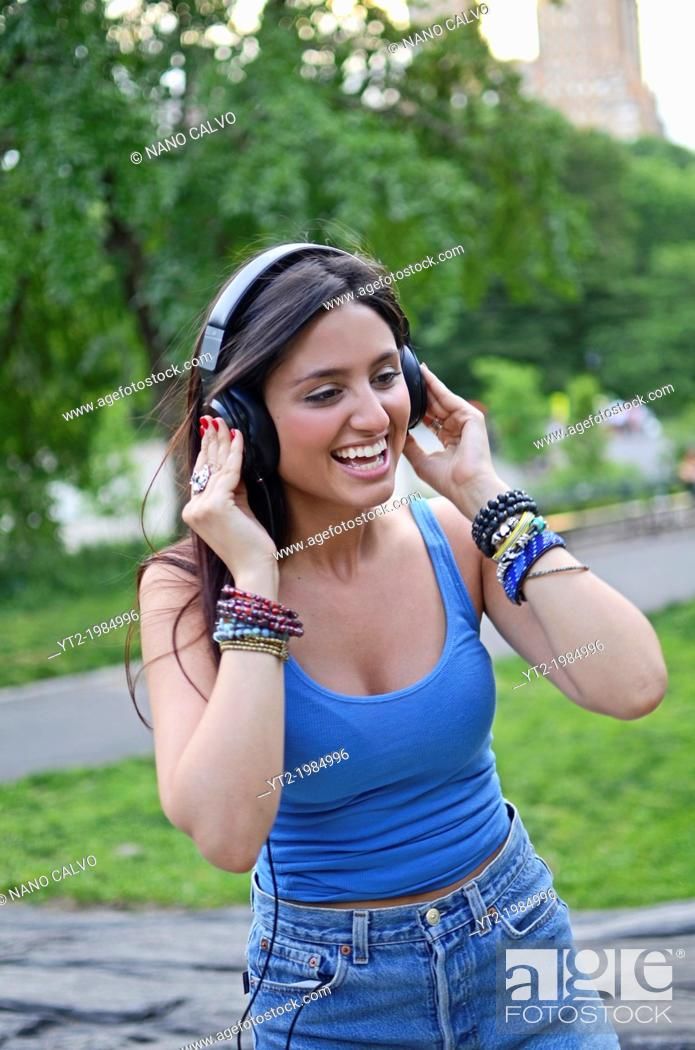 Stock Photo: Attractive young mixed race woman listening to music in Central Park, New York City.