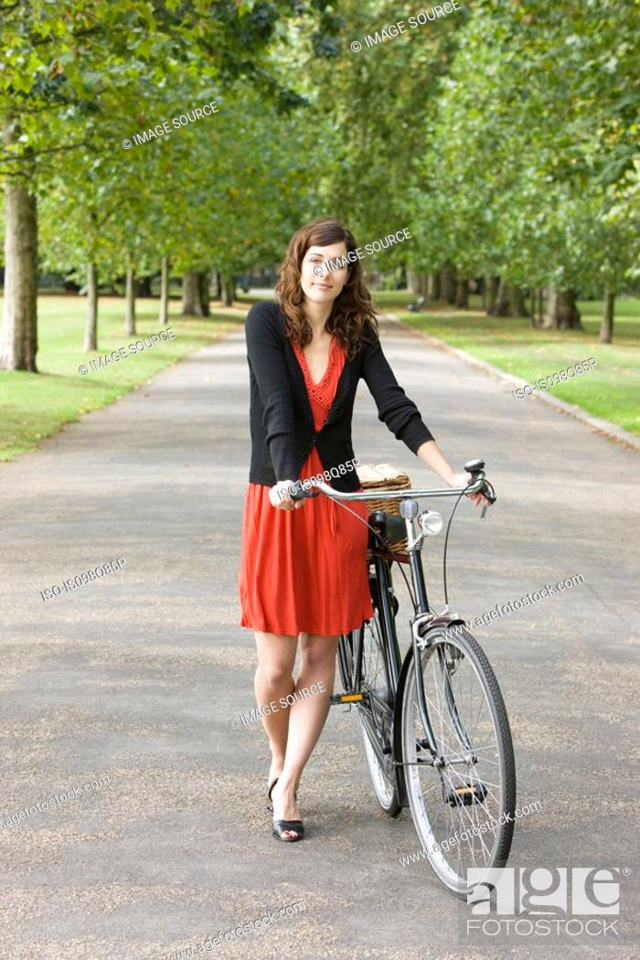 Stock Photo: Woman in park with bike.