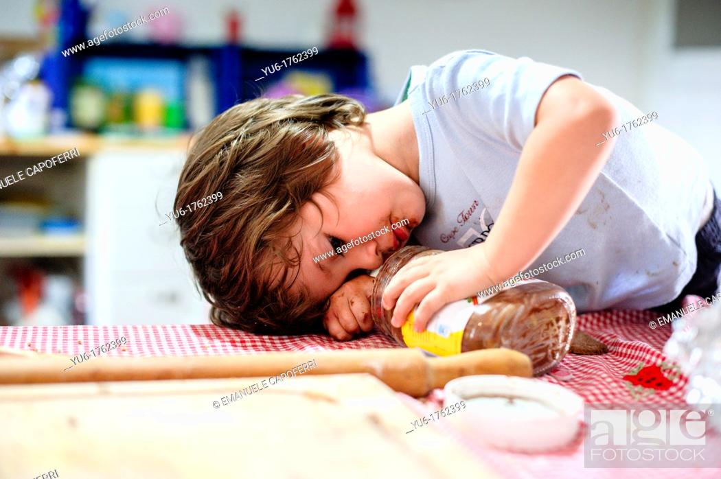 Stock Photo: Child takes chocolate from the pot.