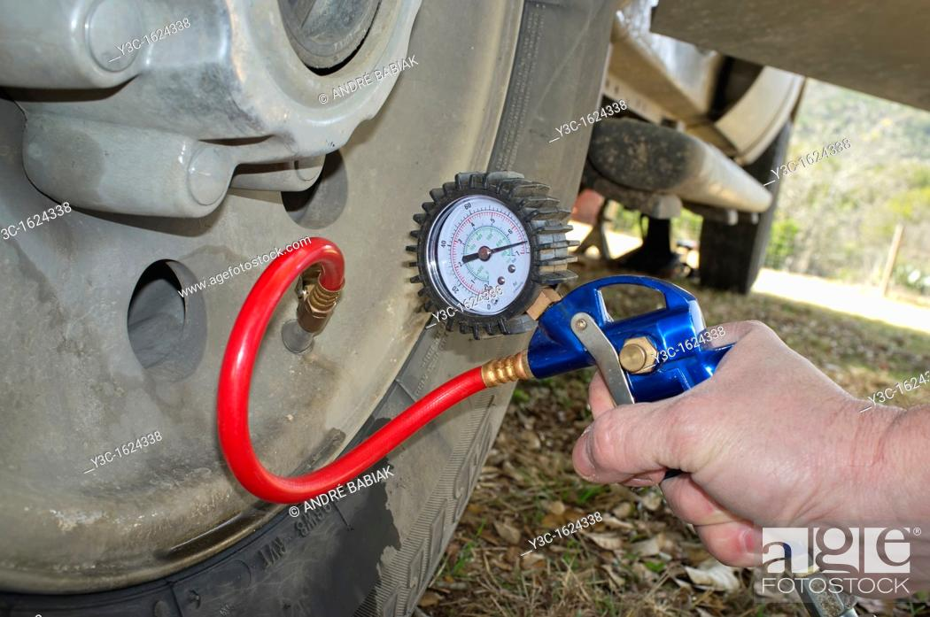 Stock Photo: Pumping up a tire - putting air pressure on with tire inflator.