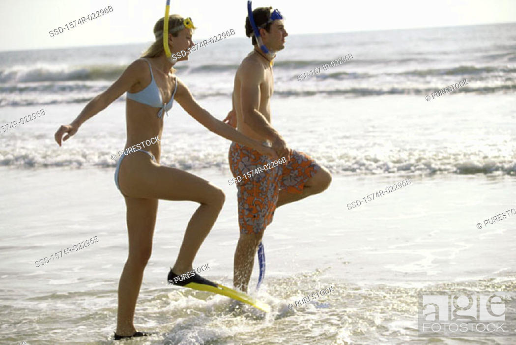 Stock Photo: Side profile of a teenage couple walking on the beach wearing snorkels and flippers.