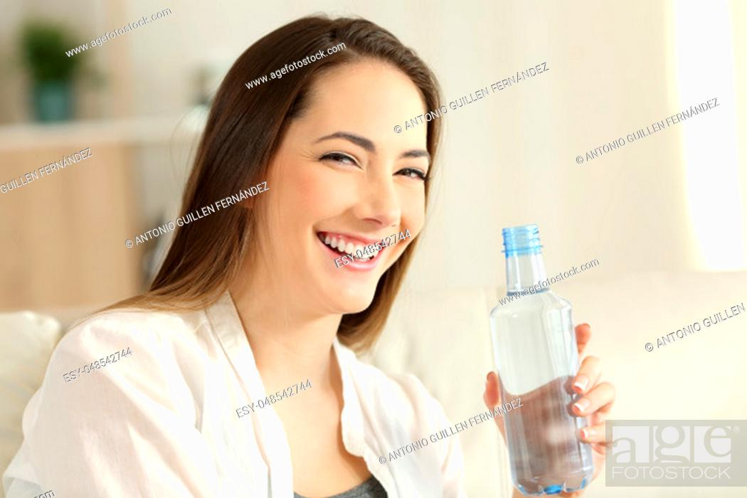 Stock Photo: Portrait of a happy woman holding a water bottle looking at you sitting on a couch in the living room at home.