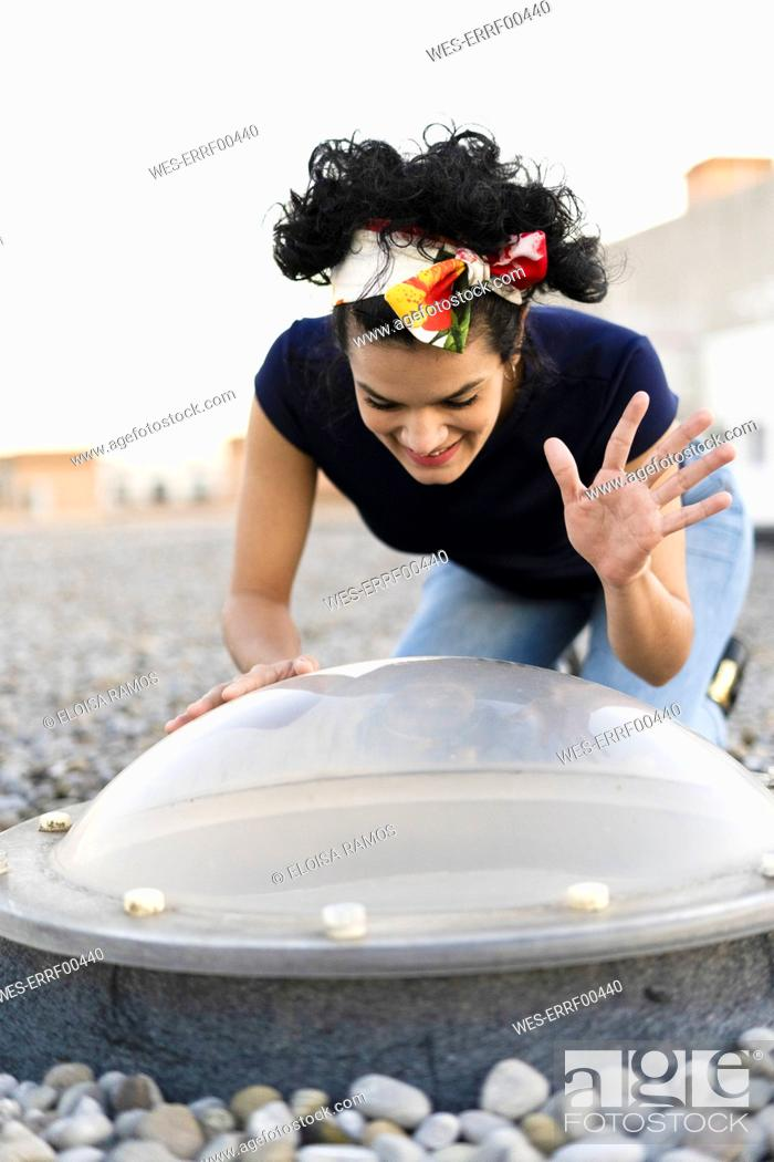 Stock Photo: Smiling young woman looking through skylight on roof terrace raising her hand.