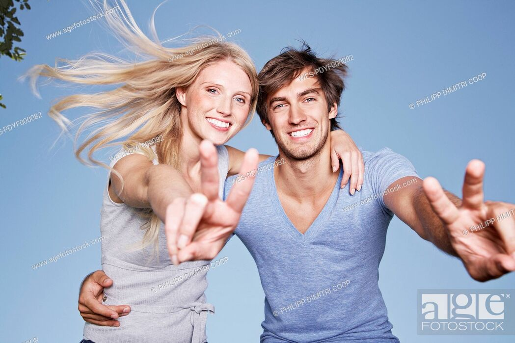 Stock Photo: Germany, Cologne, Young couple showing peace sign, smiling, portrait.