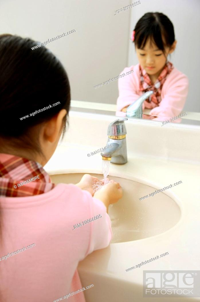 Stock Photo: Little girl washing hands under faucet.