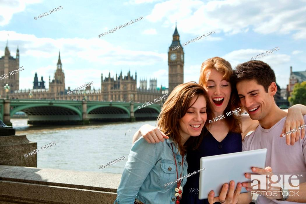 Stock Photo: Friends looking at a digital tablet together in London.