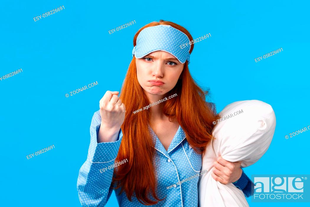 Stock Photo: Who disturbed my sleep. Mad and displeased, angry grumpy redhead woman threaten sibling being too loud in morning, shaking fist frowning, holding pillow.