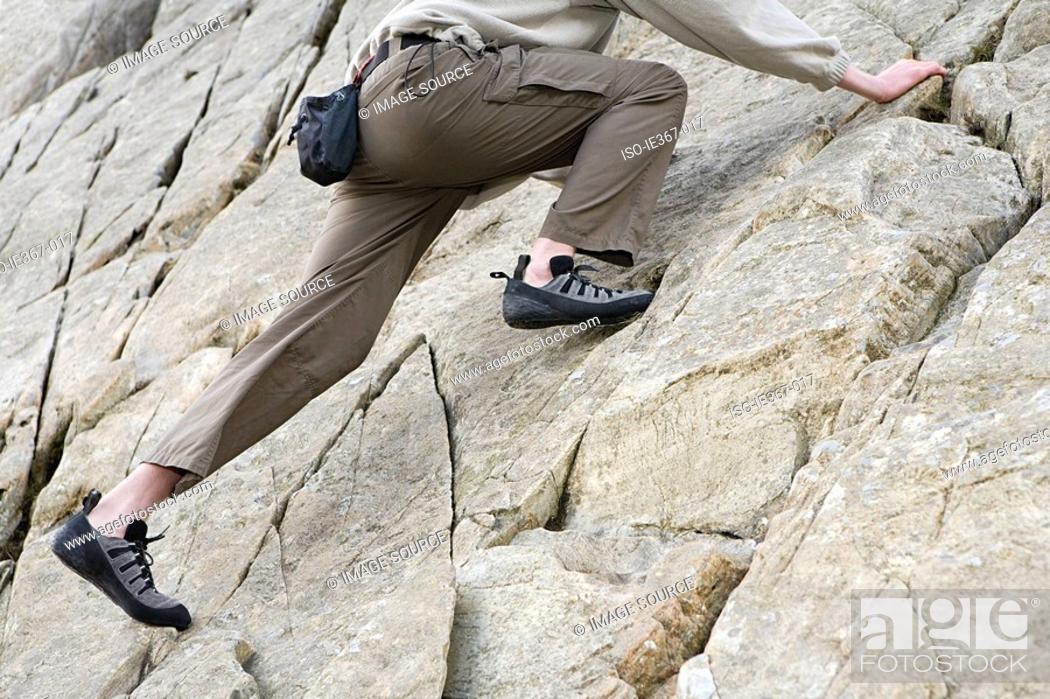 Stock Photo: A person rock climbing.