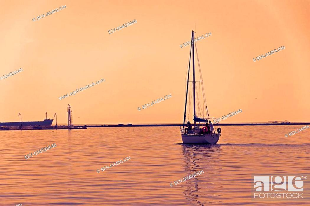 Stock Photo: Departuring yacht in late sunset.