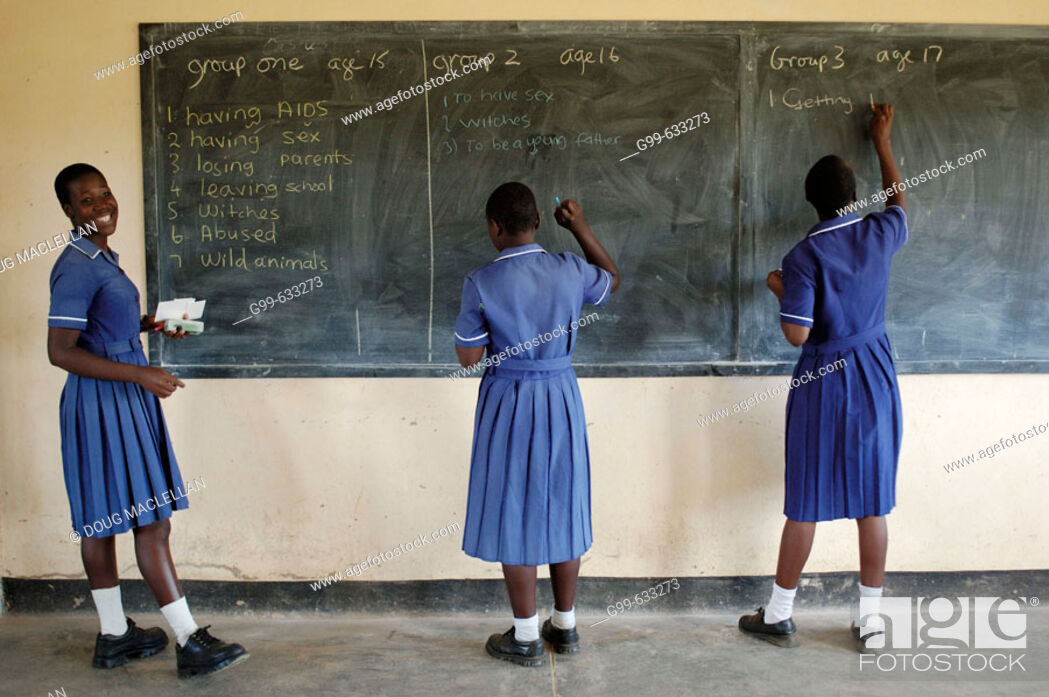 Stock Photo: Three members of the Nyachuru High School AIDS Club write on the chalkboard a list of the their fears. The exercise is prompted by a Canadian guest lecturer.