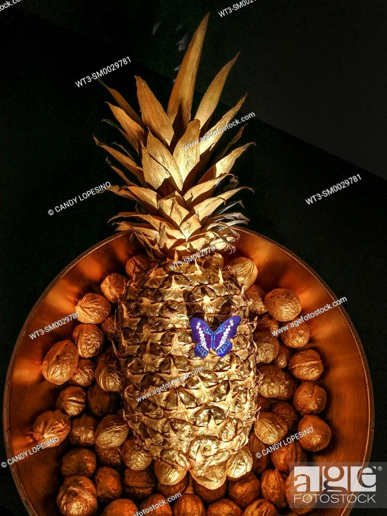 Stock Photo: Pineapple with blue butterfly in golden tray of walnuts on black background.