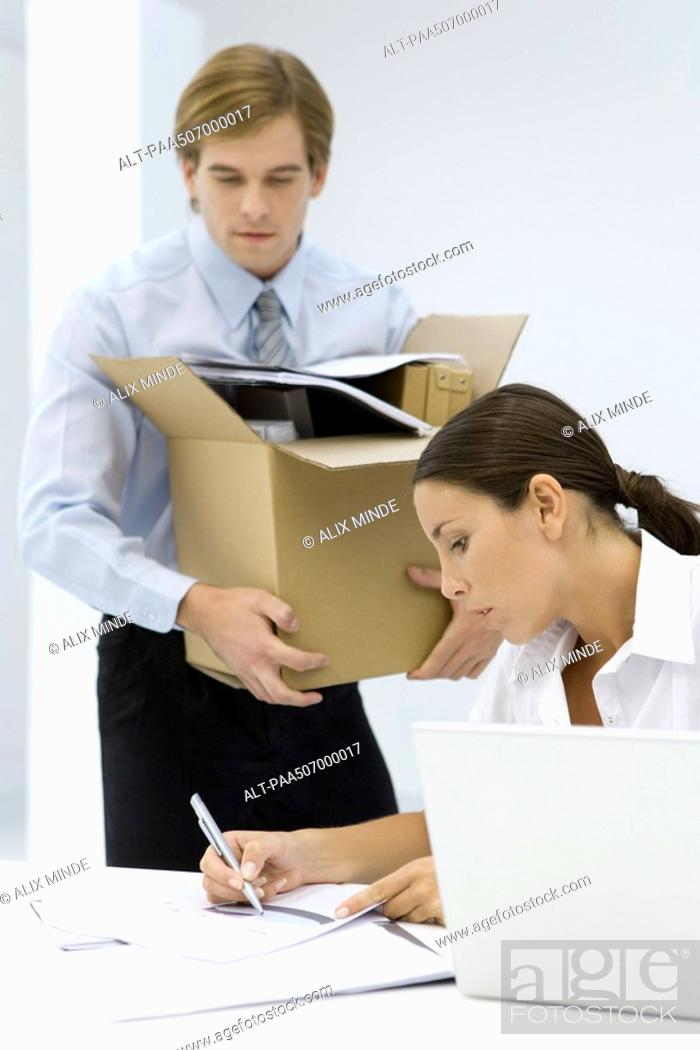 Stock Photo: Woman writing on document at desk, man carrying cardboard box full of office supplies.