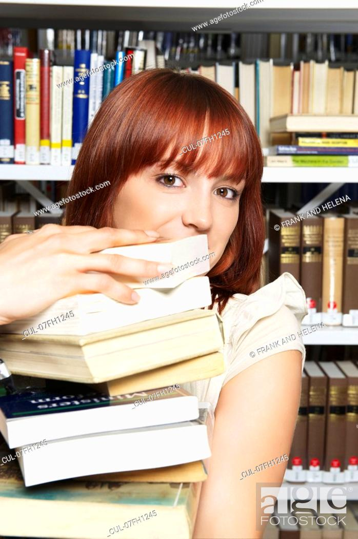 Stock Photo: Young woman carrying pile of books.