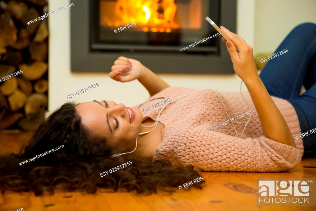 Stock Photo: Beautiful woman listen music at home at the warmth of a fireplace.