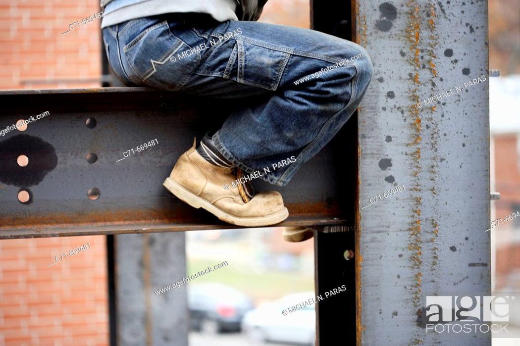 Stock Photo: Construction iron worker sitting on I beam.