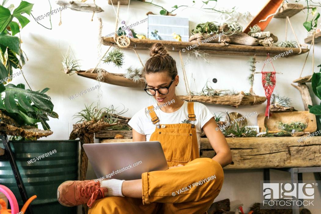 Stock Photo: Young woman using laptop in a small gardening shop.