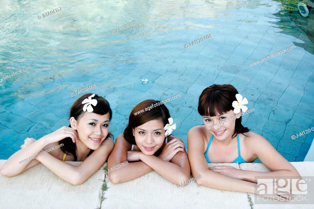 Stock Photo: Portrait of three teenage girls in swimming pool.